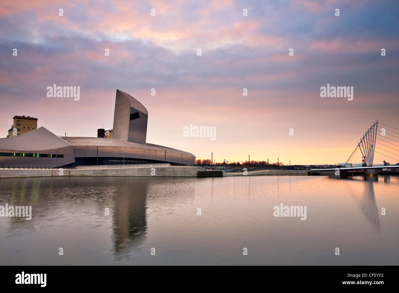 Imperial War Museum North (IWM North) in a spectacular building designed by Daniel Libeskind and the Lowry Bridge - Stock Image