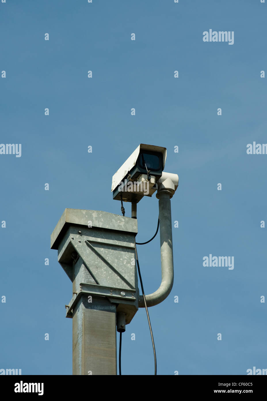 A CCTV (closed circuit television) camera on top of a tall pole surveying the traffic passing along the M25 in Essex. - Stock Image