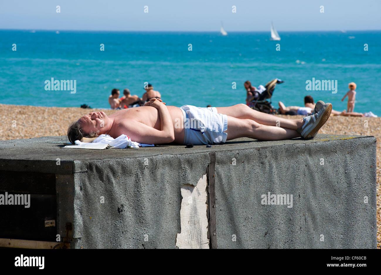A man sunbathing on top of a deckchair hut on Brighton beach. - Stock Image