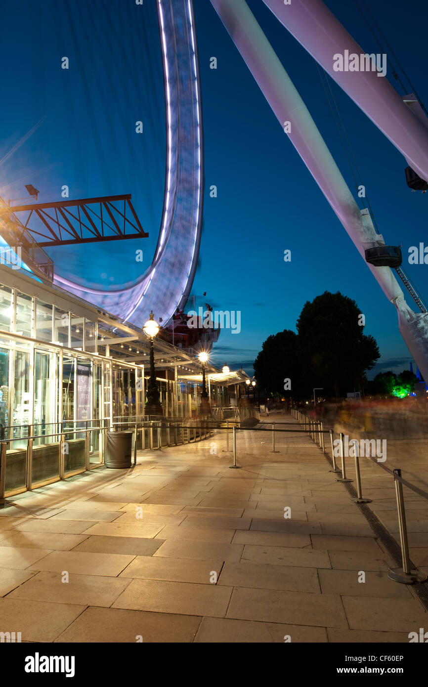 The embarkation point of the London Eye on the South Bank at night. - Stock Image
