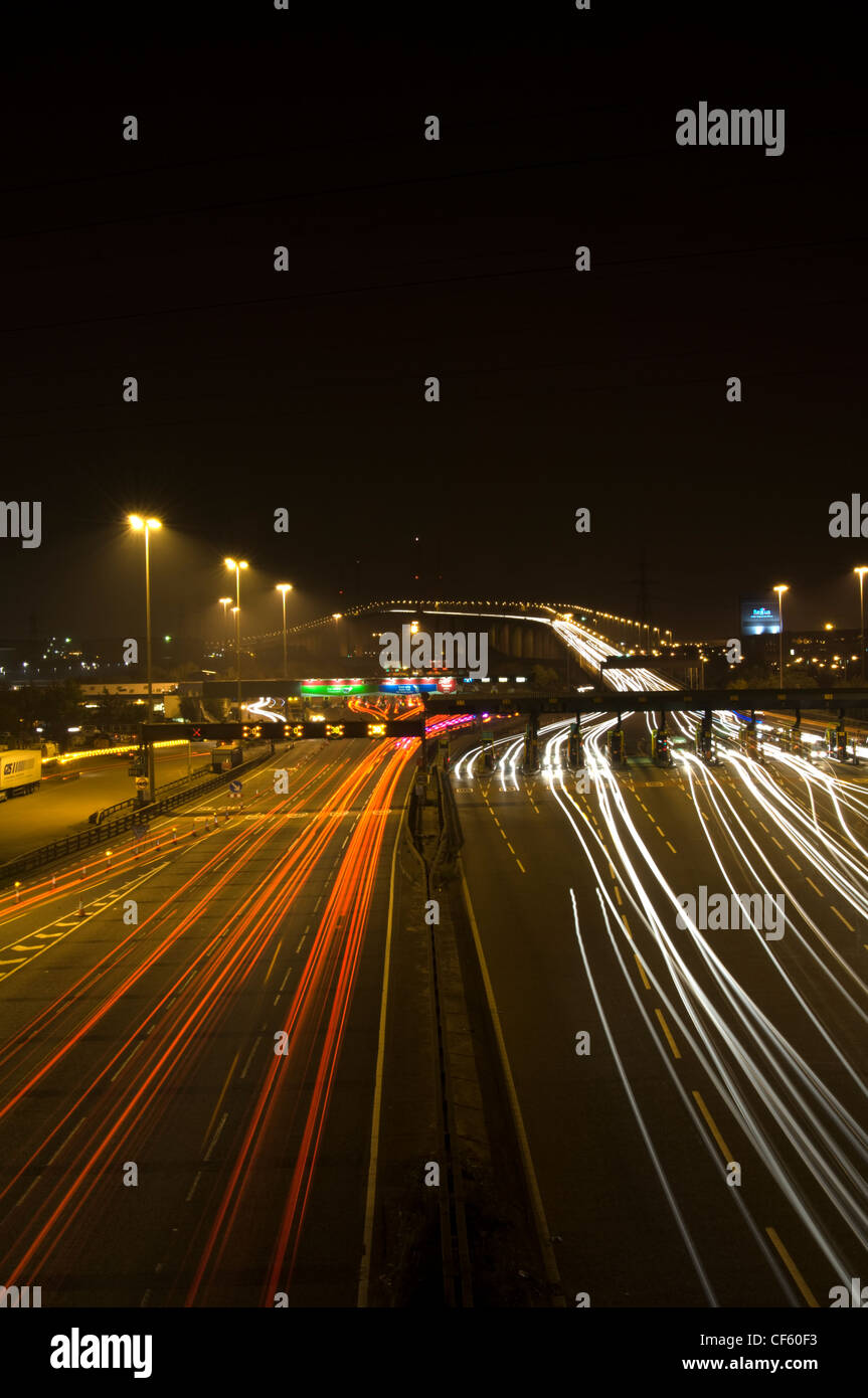 Light trails from vehicles travelling to and from the Dartford River Crossing at night. - Stock Image