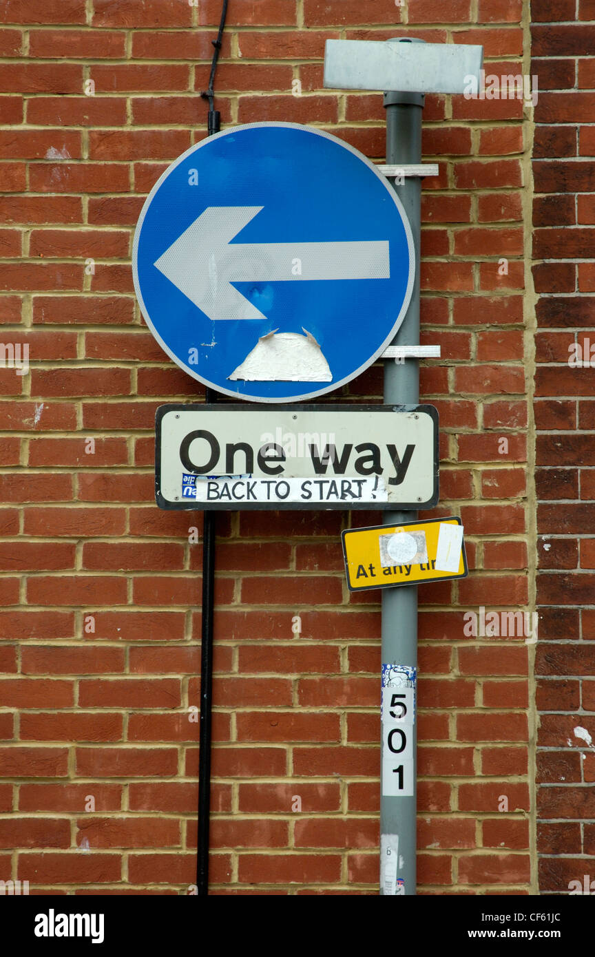 One Way road sign with a humourous sticker posted on it. - Stock Image