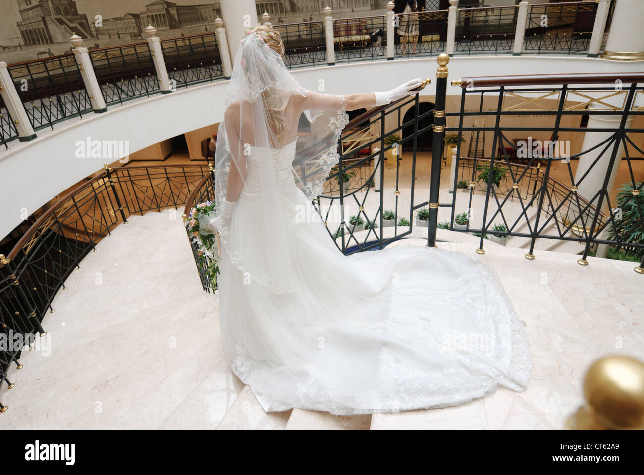 Bride in beautiful wedding dress stands on broad staircase, rear view. - Stock Image