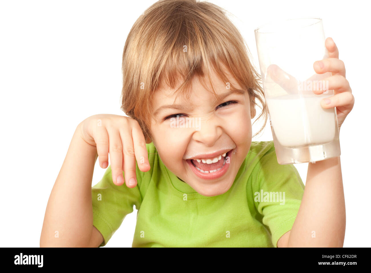 small girl in green blouse wriggles and drinks tasty fresh milk - Stock Image