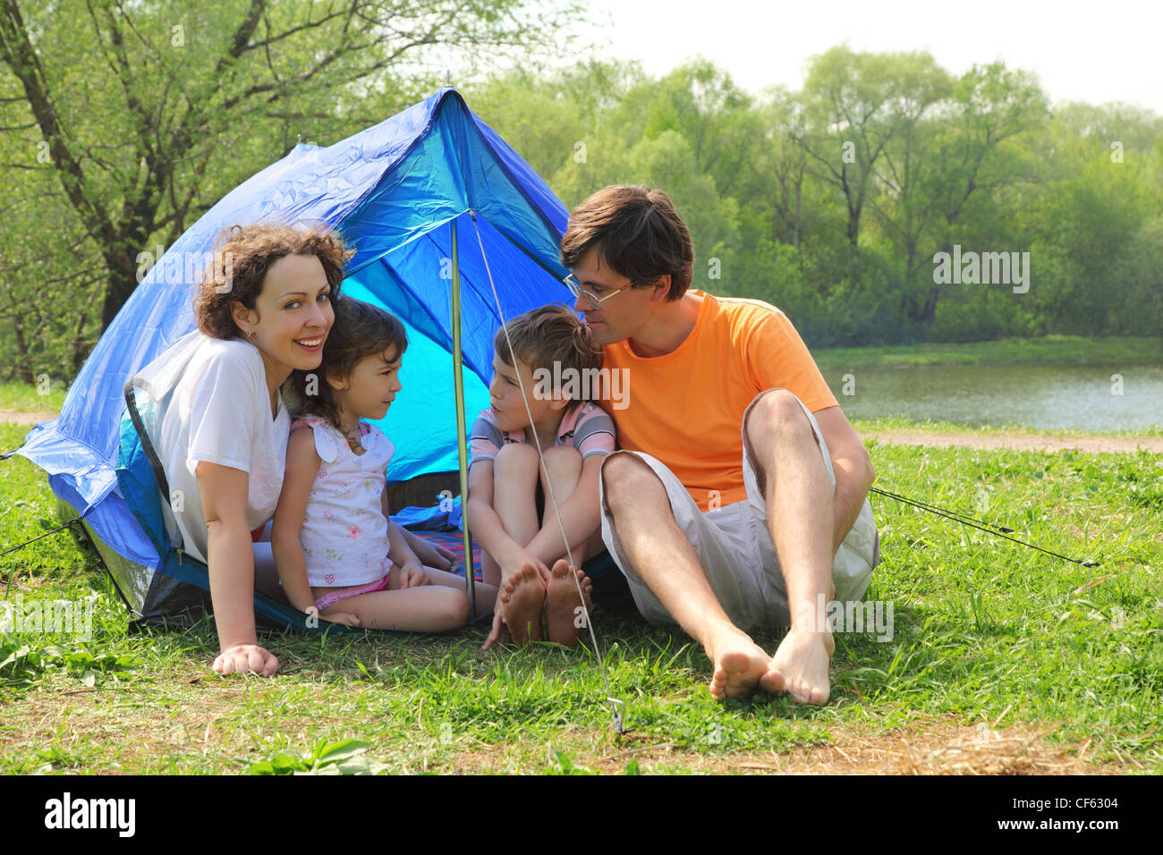 Happy family - mother, father, little girl and boy - sitting in blue tent on green lawn on bank of river at sunny Stock Photo