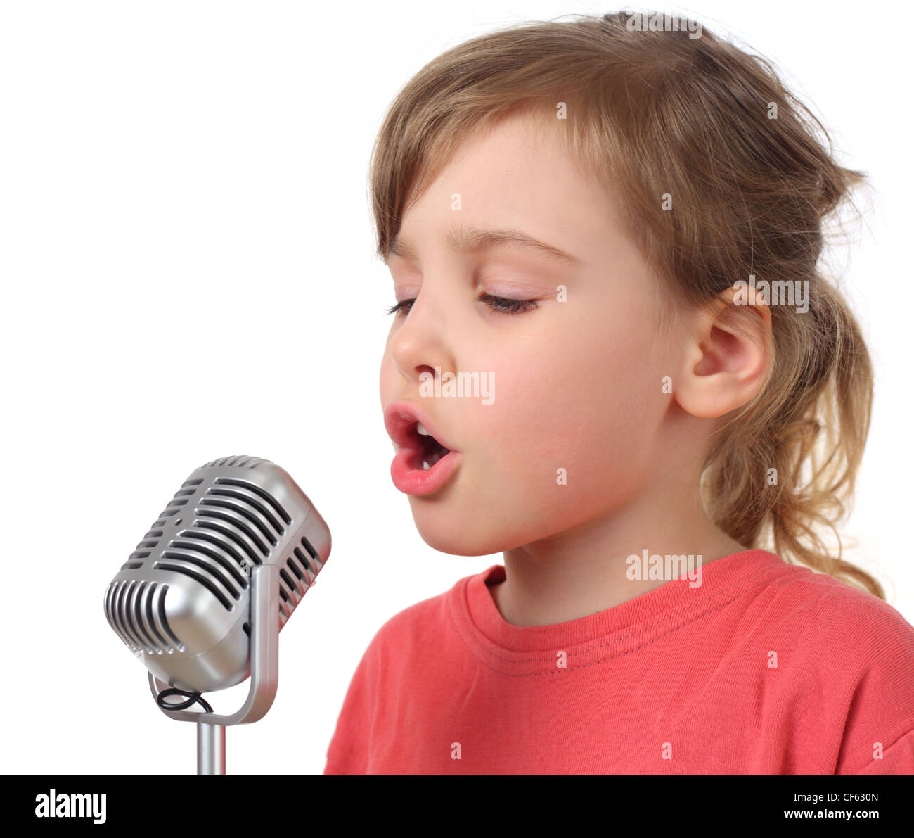 little girl in red shirt singing in microphone, half body, isolated - Stock Image