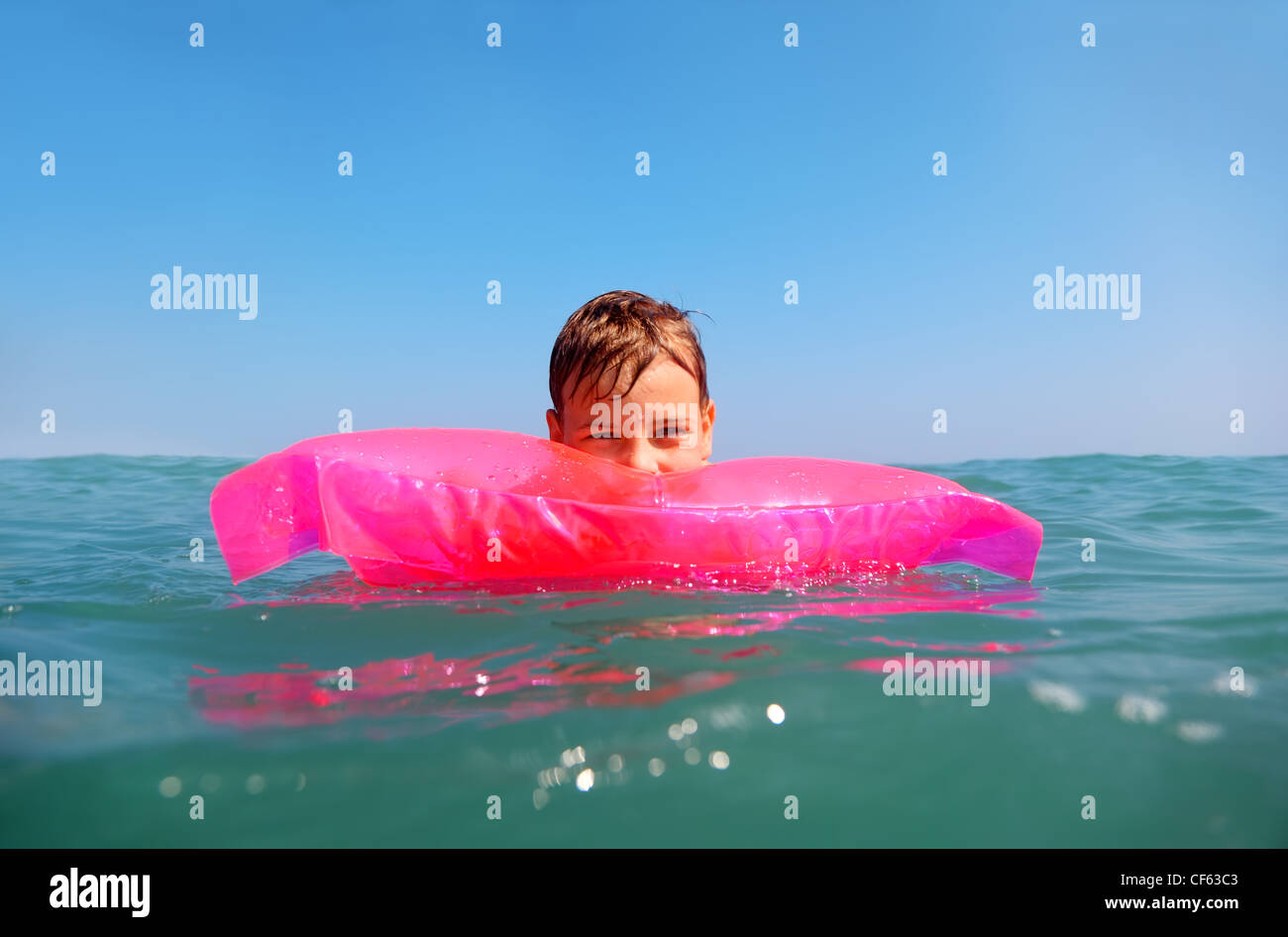 The little boy floating in sea on inflatable pink matrese. shot from underwater box, water on box blurry - Stock Image