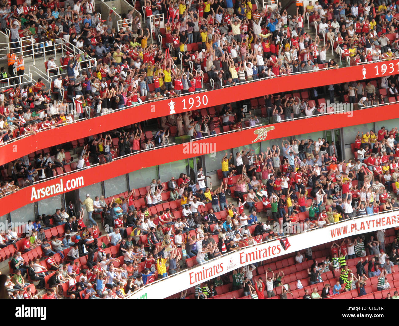 Fans participating in a 'Mexican wave' during the Emirates Cup tournament at Arsenal's Emirates Stadium. - Stock Image