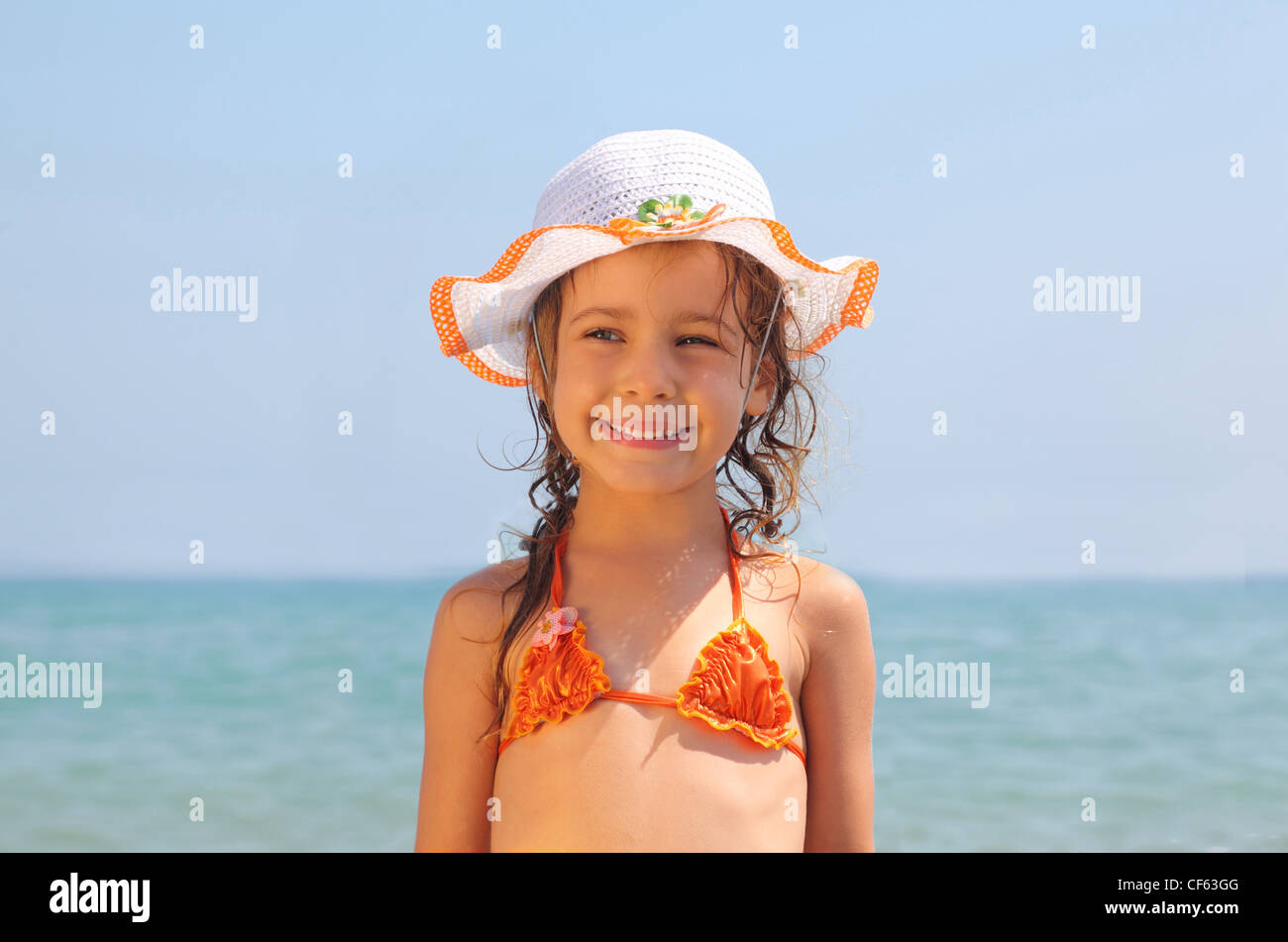 37057c66cd79a beautiful little girl, dressed in bathing suit and hat standing on beach.