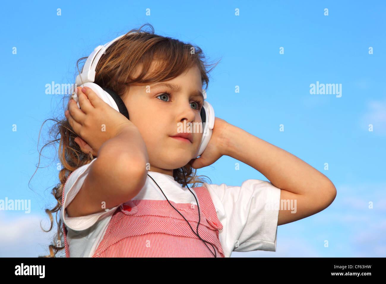 The lovely little girl, against the blue sky, listens to music through ear-phones. - Stock Image