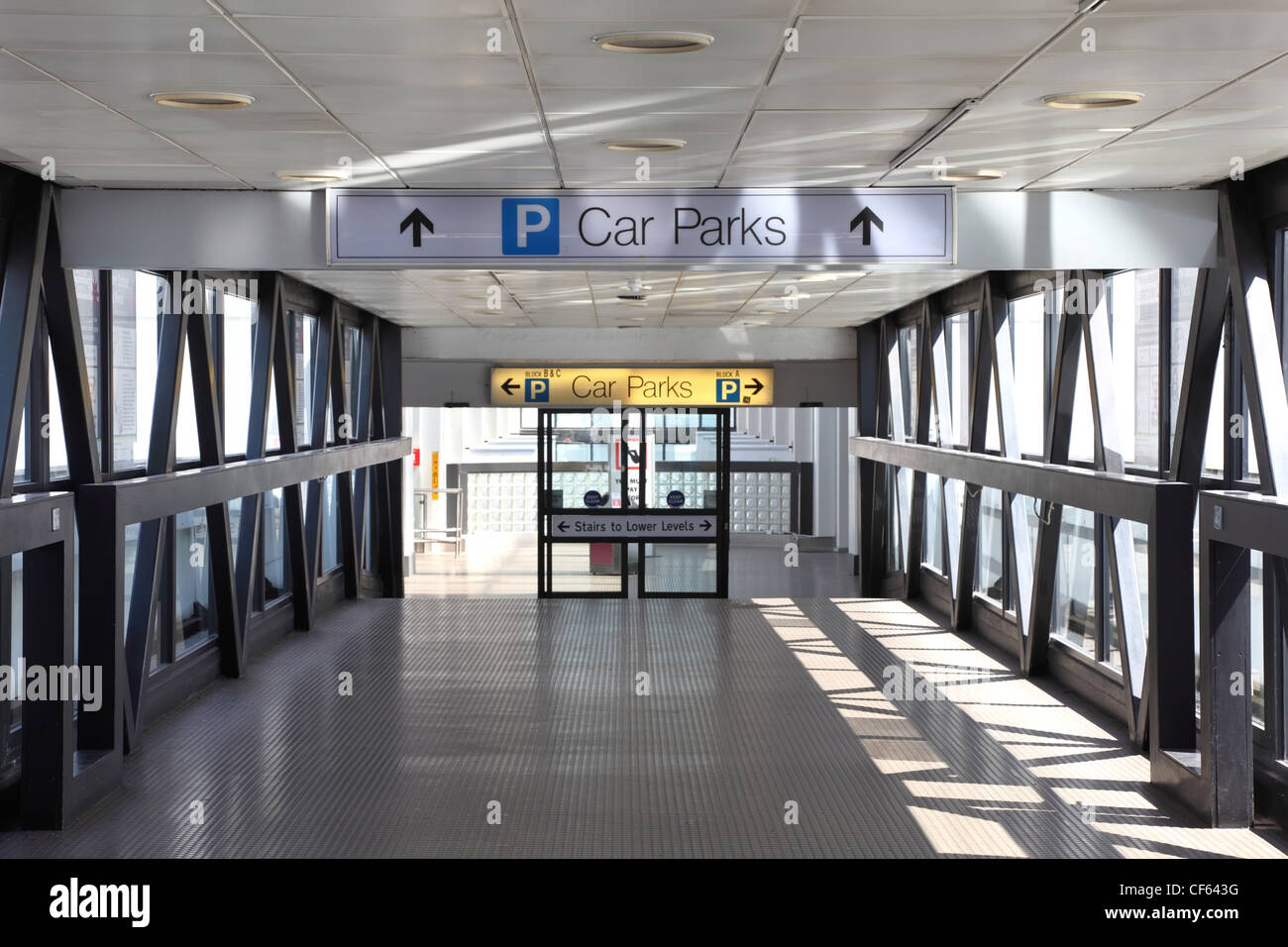 entrance to parking lot. glass doors, sunlight shines through large windows - Stock Image