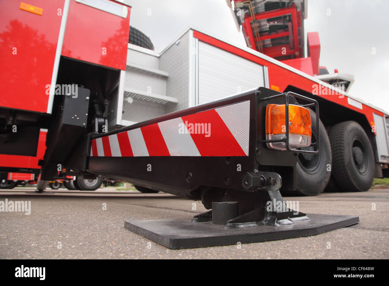 Bottom view of at the pull-out support of big red fire engine at day - Stock Image