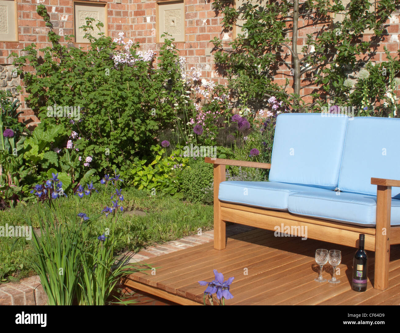 oyal Horticultural Society Chelsea Flower Show in London Comfortable outdoseating, set on decking beside a small, - Stock Image
