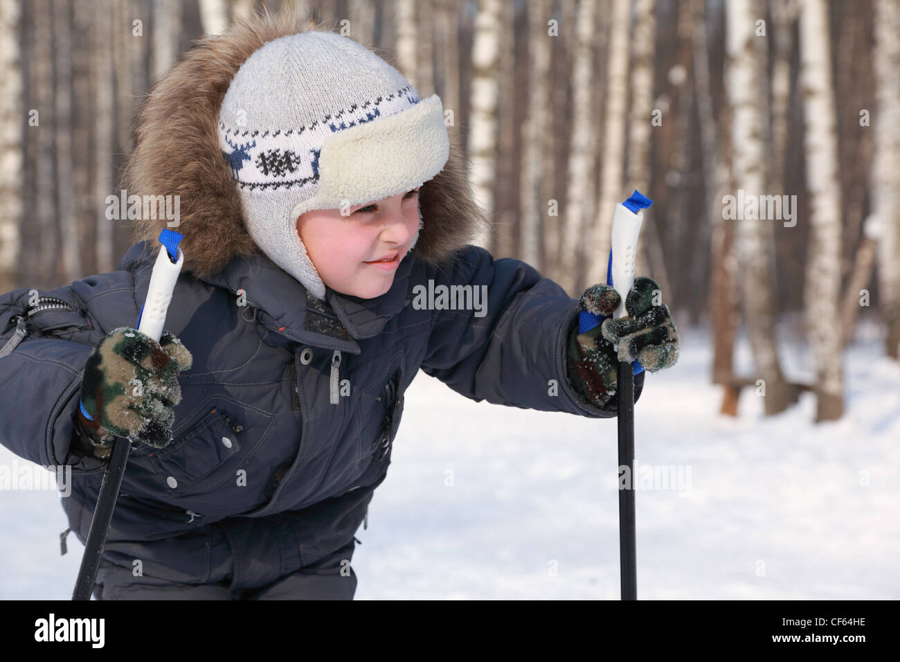 Portrait of young boy with ski poles looking to side inside winter forest at sunny day - Stock Image
