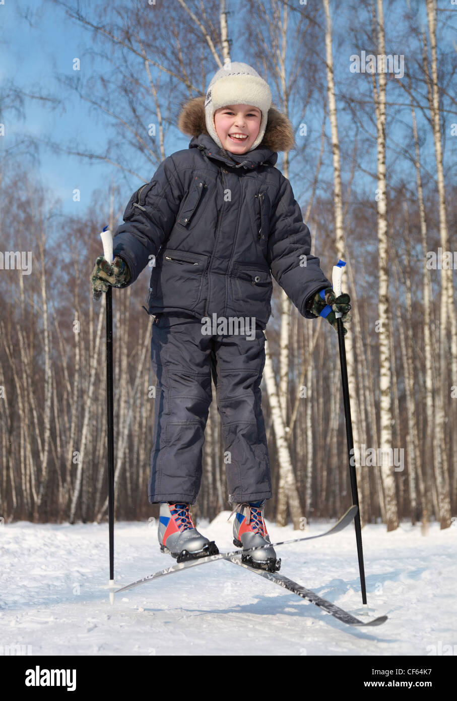 Young boy jumps and crosses cross-country skis inside winter forest at sunny day - Stock Image