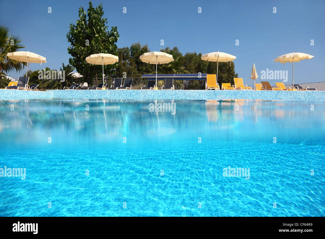 Pool is under open-skies laid out  inlaid tile on verge of which deck-chairs stand with umbrellas, underwater half Stock Photo
