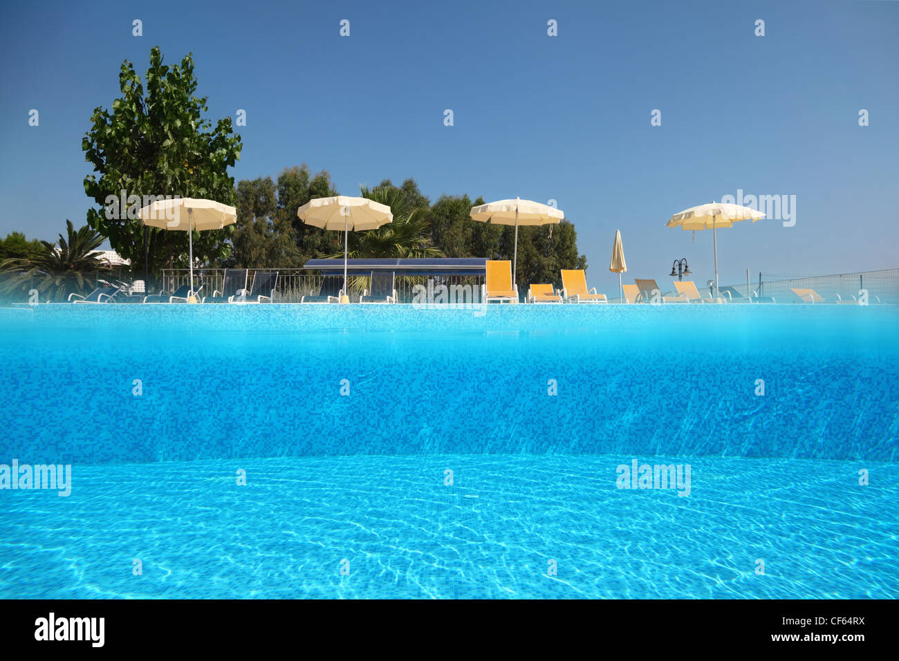 Pool Under Open Skies On Edge Of Which Deck Chairs Stand With Umbrellas,  Underwater Half Photo