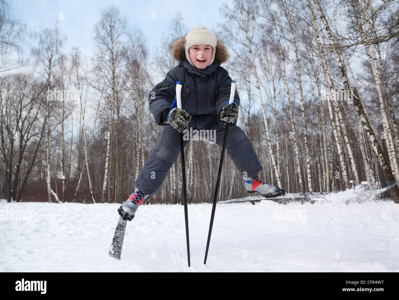 Young boy jumps and spreads legs on cross-country skis inside winter forest at sunny day - Stock Image