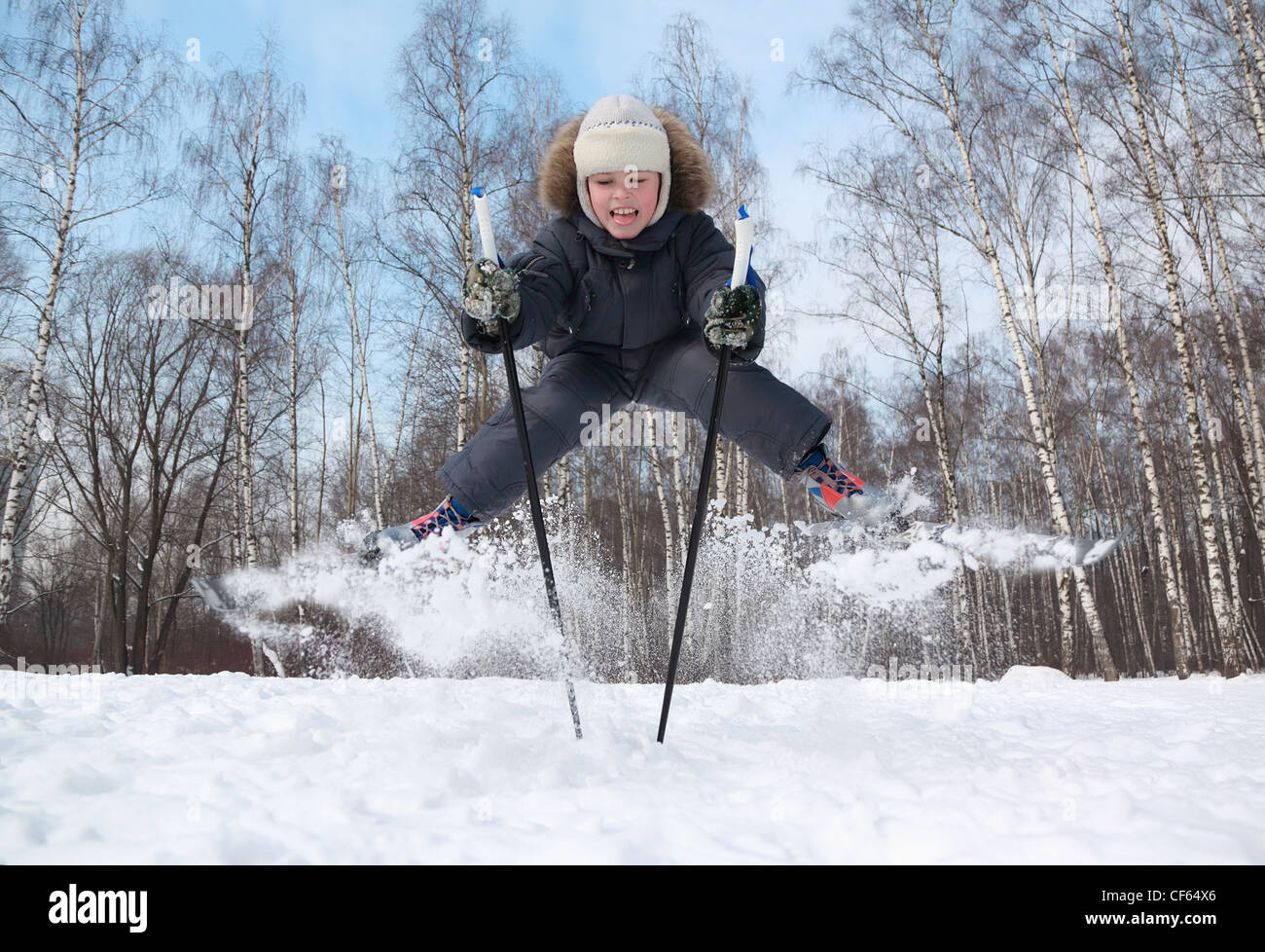 Young boy with cross-country skis and poles jumps and tongue out inside winter forest at sunny day - Stock Image