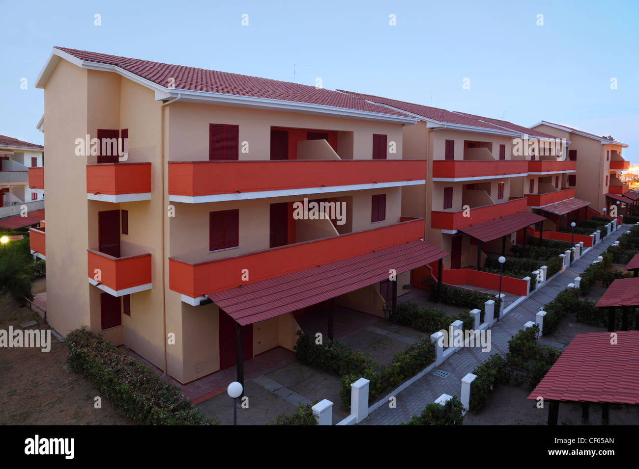 Three-storeyed cottages stand even rows and little street between them Stock Photo