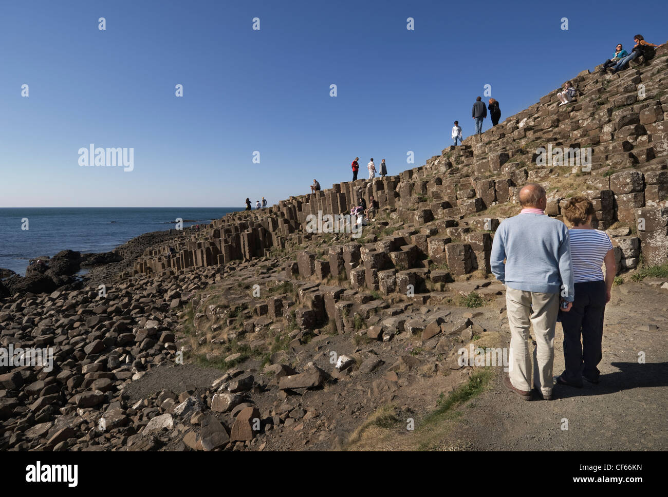 Tourists enjoying the wonder of the Giants Causeway, formed from 40,000 interlocking basalt columns. The Giants Stock Photo