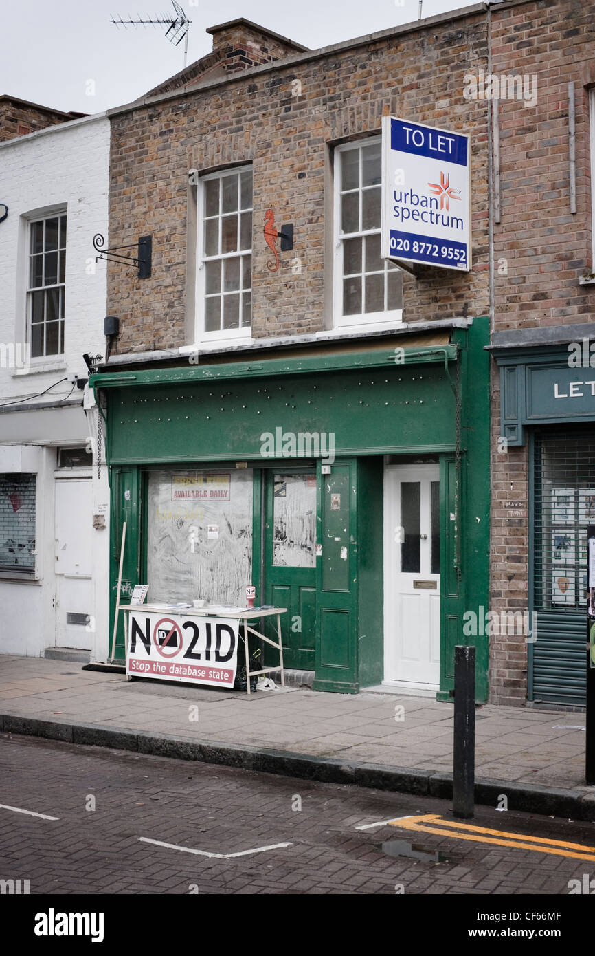 No to National ID cards stand in front of a boarded up shop. - Stock Image
