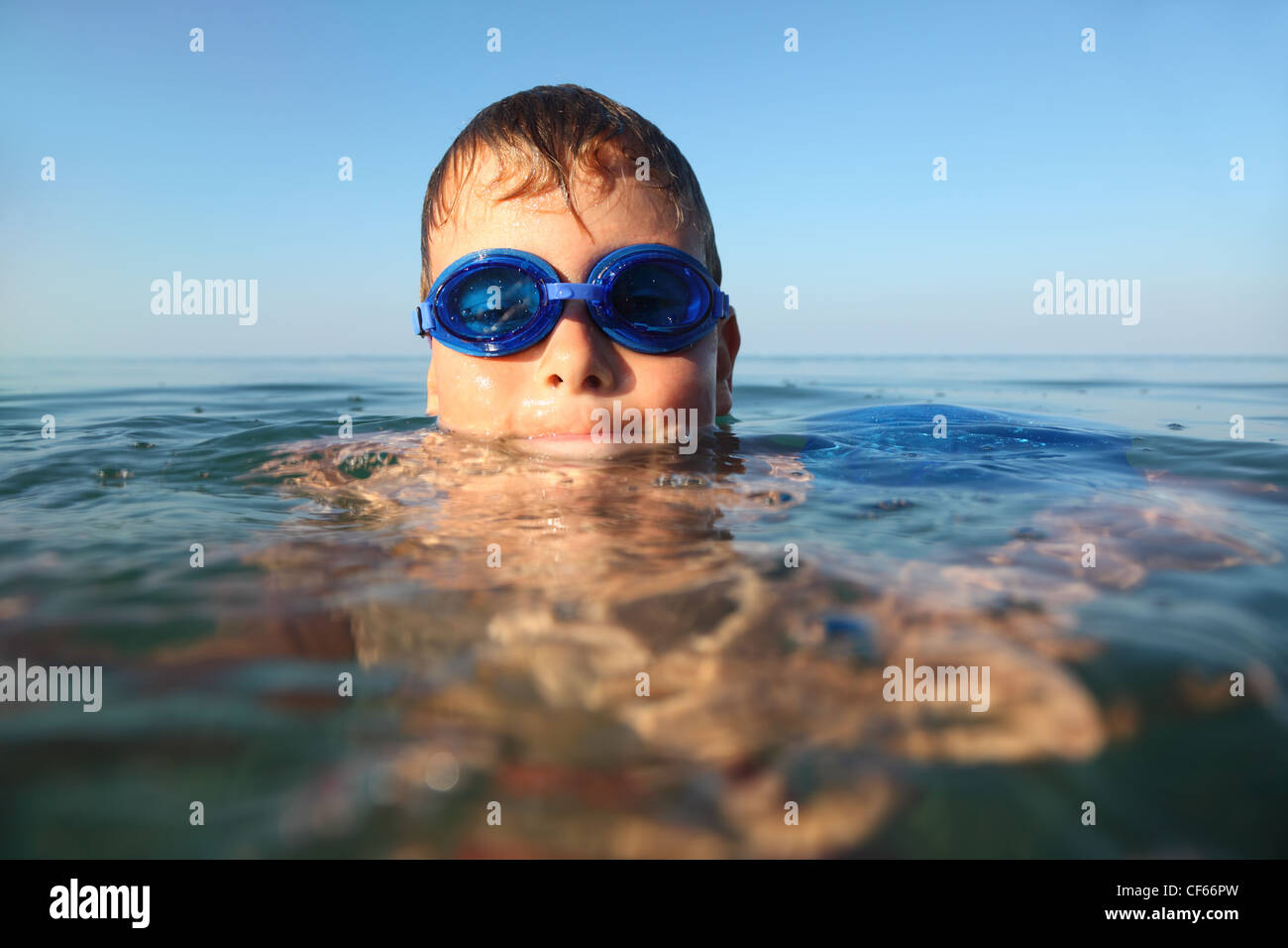 boy in blue spectacles for swimming swims in the sea. blue sky. hot summer - Stock Image
