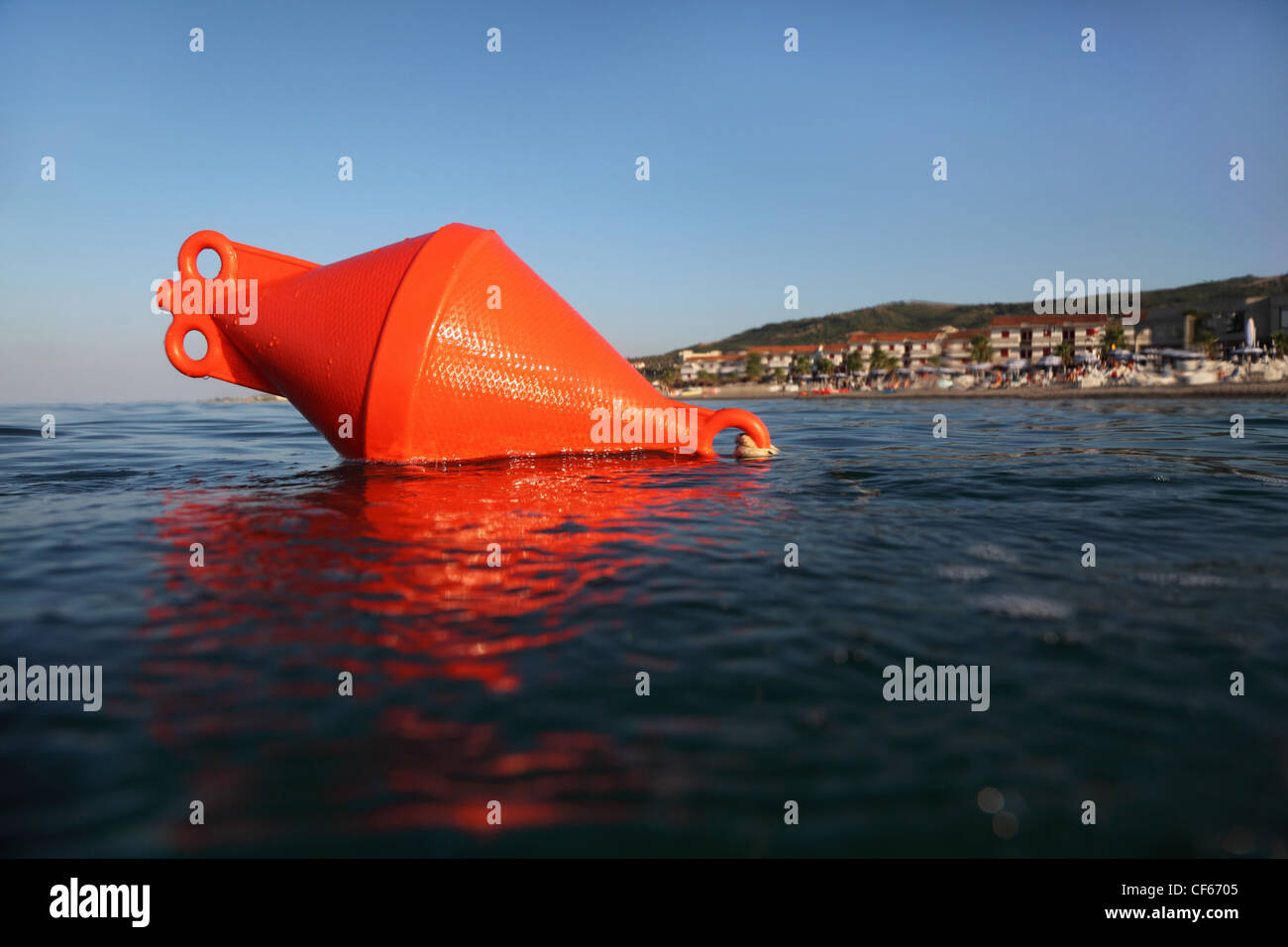 orange anchor buoy floats on the sea. beach could be seen in the distance - Stock Image