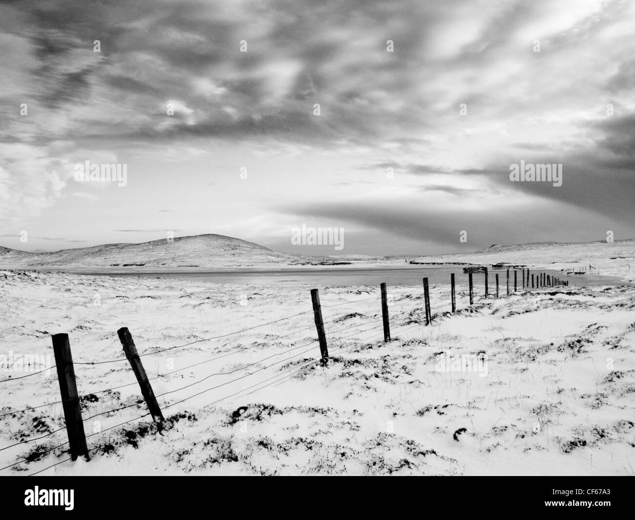 Overcast snowy day at Tresbister Ness on Shetland. - Stock Image