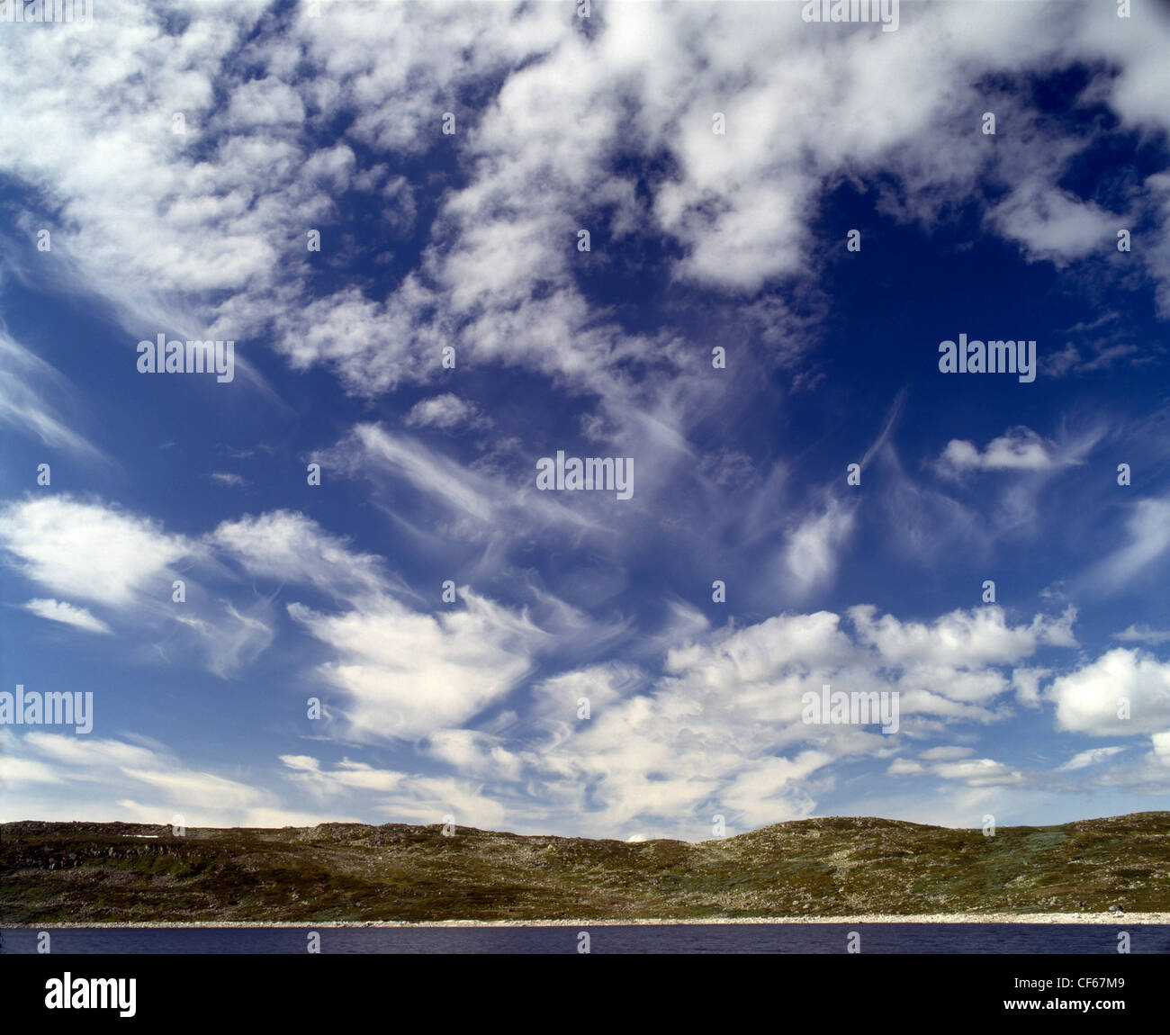 Cirrus clouds with horizon and sea.  A cirrus cloud is Latin for 'wisp of hair' and is composed of ice crystals - Stock Image