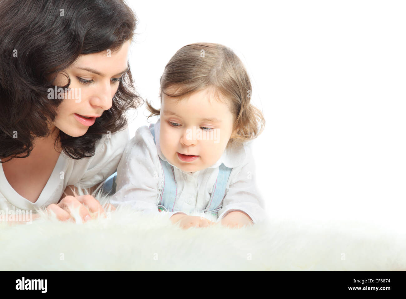 Thoughtful mother and her little daughter lie on white fluffy rug - Stock Image