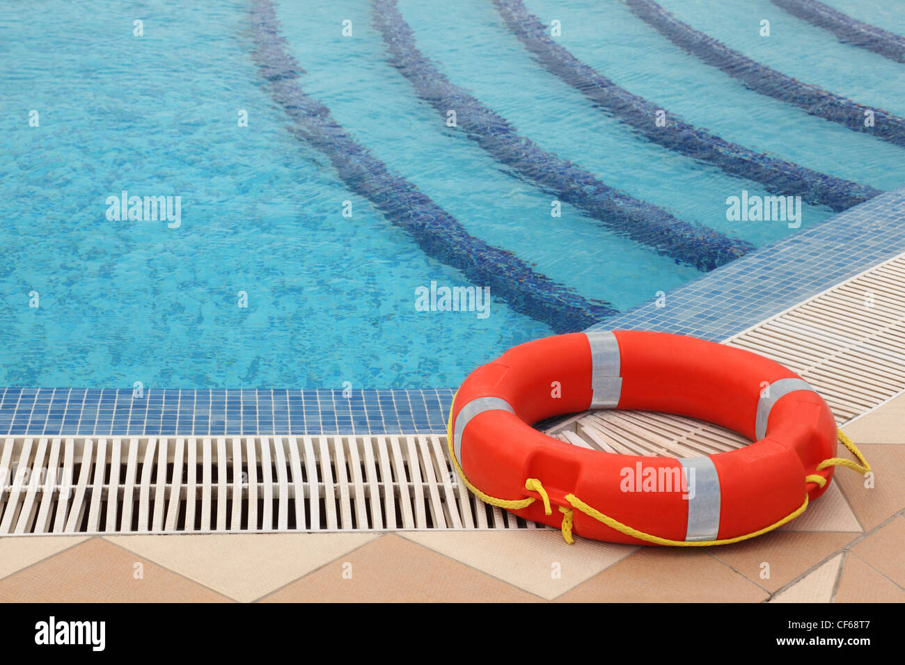 red lifebuoy with yellow ropes on tiled floor near swimming pool with stairs - Stock Image