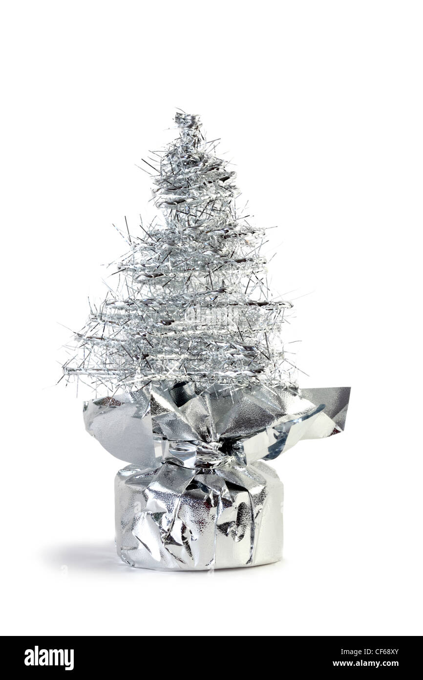 Silver artificial Christmas tree made of tinsel grows from gift wrapping - Stock Image