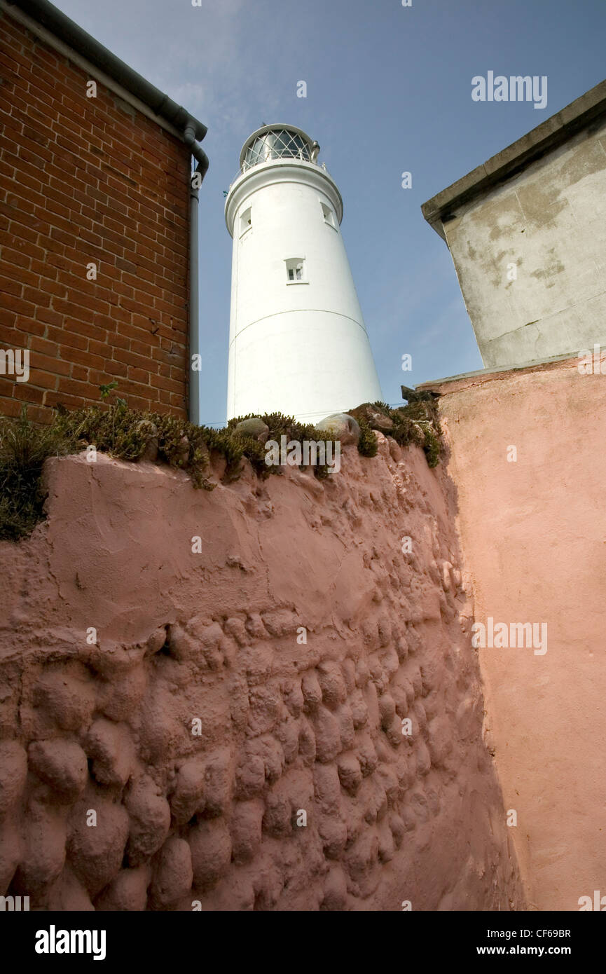 Suffolk pink wall and Southwold Lighthouse. The Lighthouse station was electrified and automated in 1938. - Stock Image