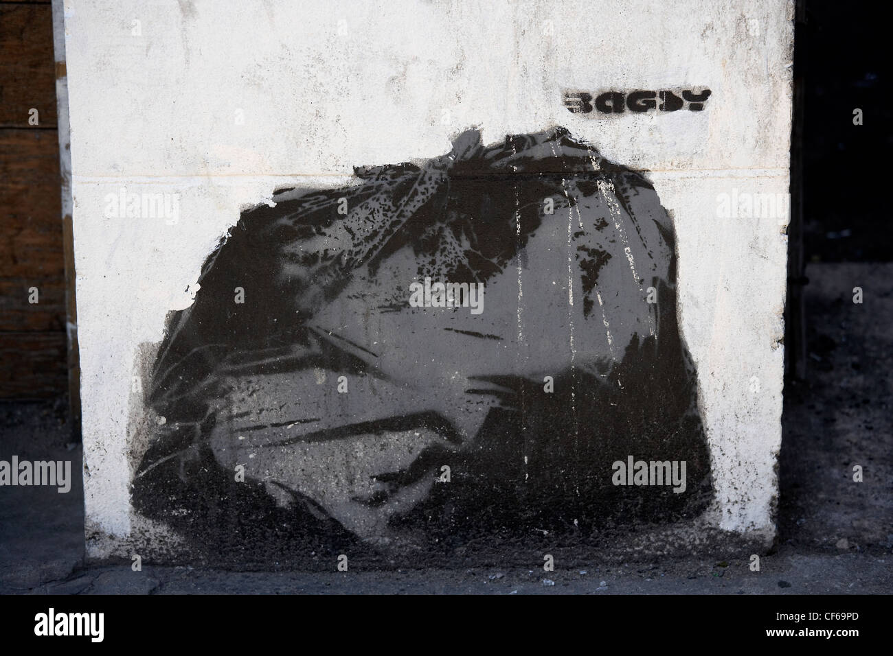 Stencil graffiti of a bin liner on a wall in Kingsland road. - Stock Image