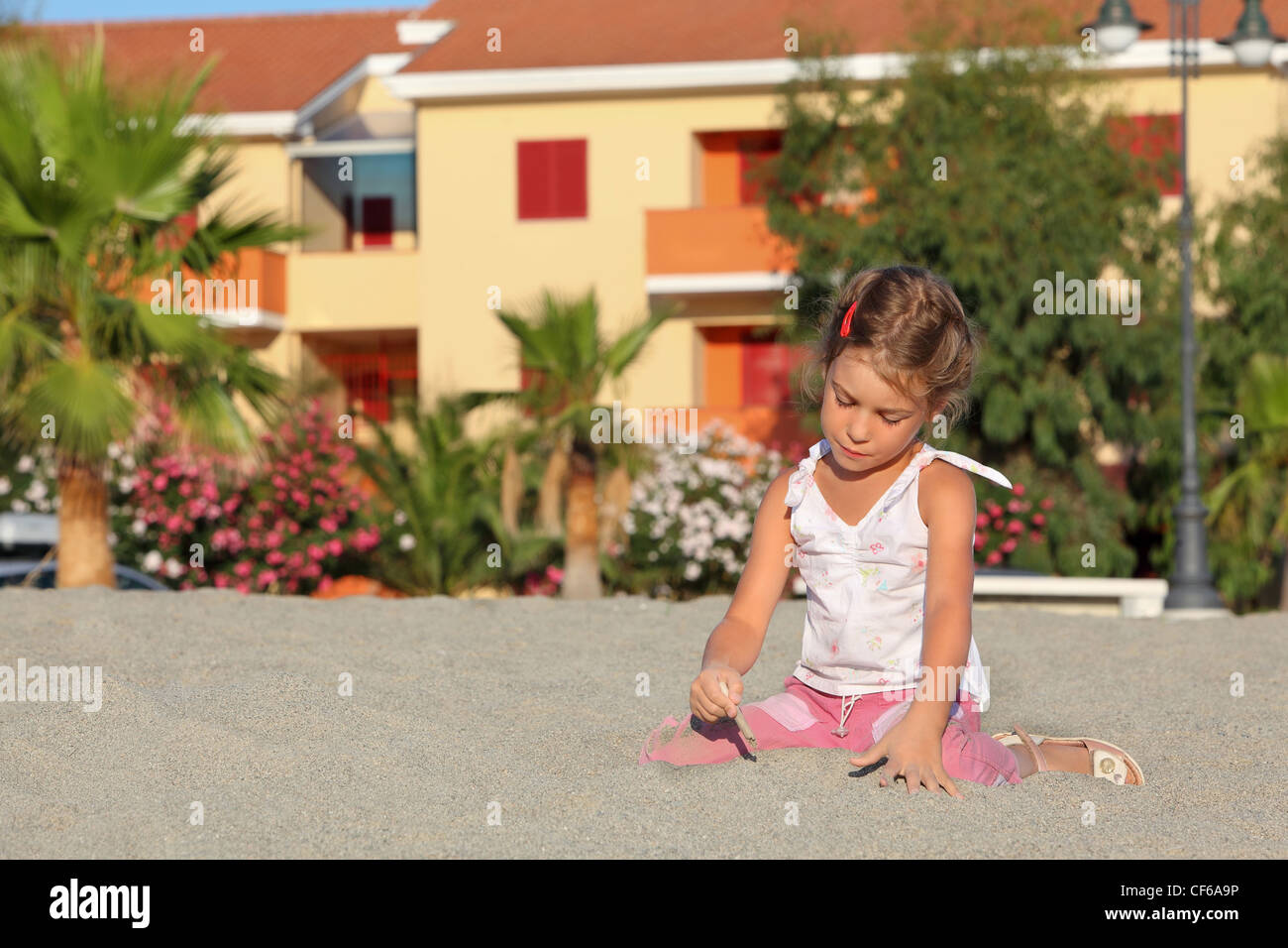 Girl sits in day-time on  beach and interestedly leads  little stick on sand - Stock Image