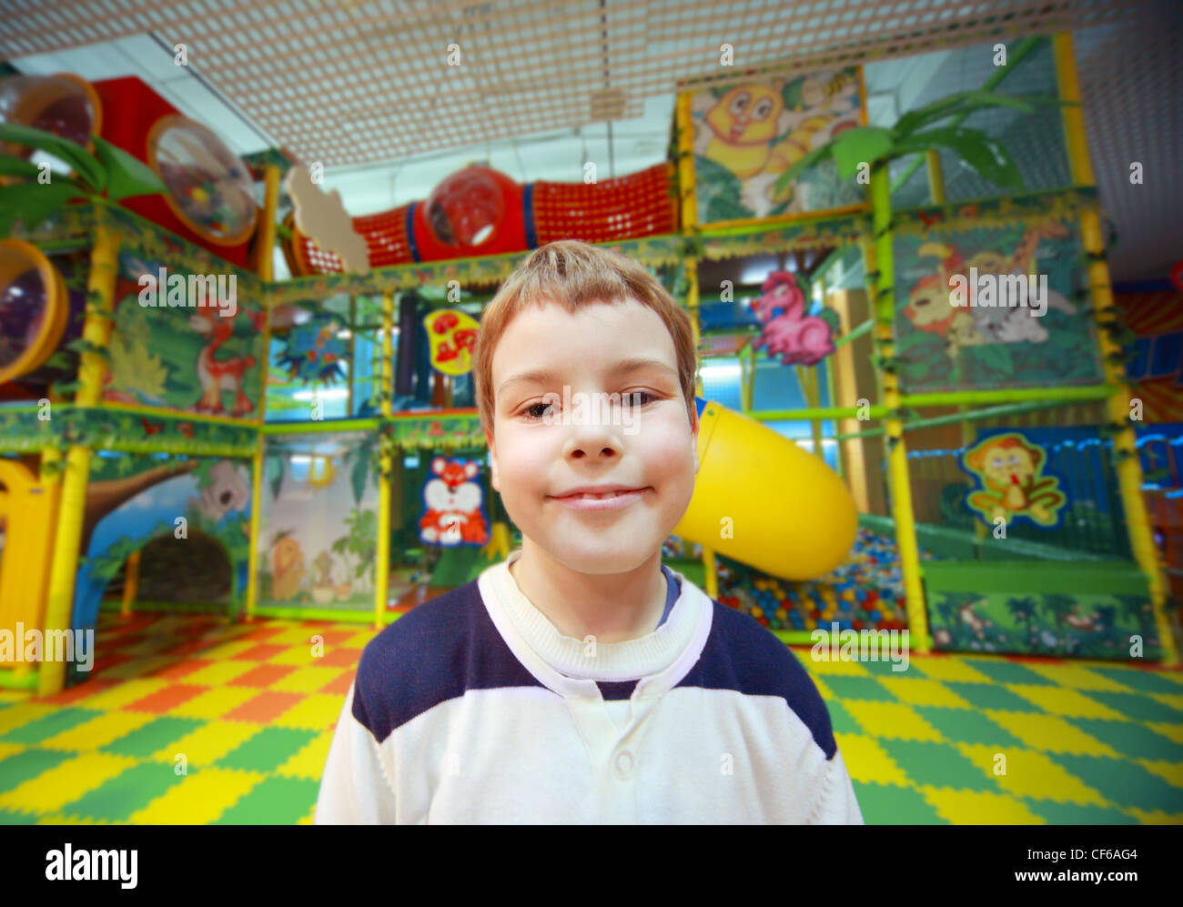Portrait of little happy boy, he plays inside adventure playground city - Stock Image