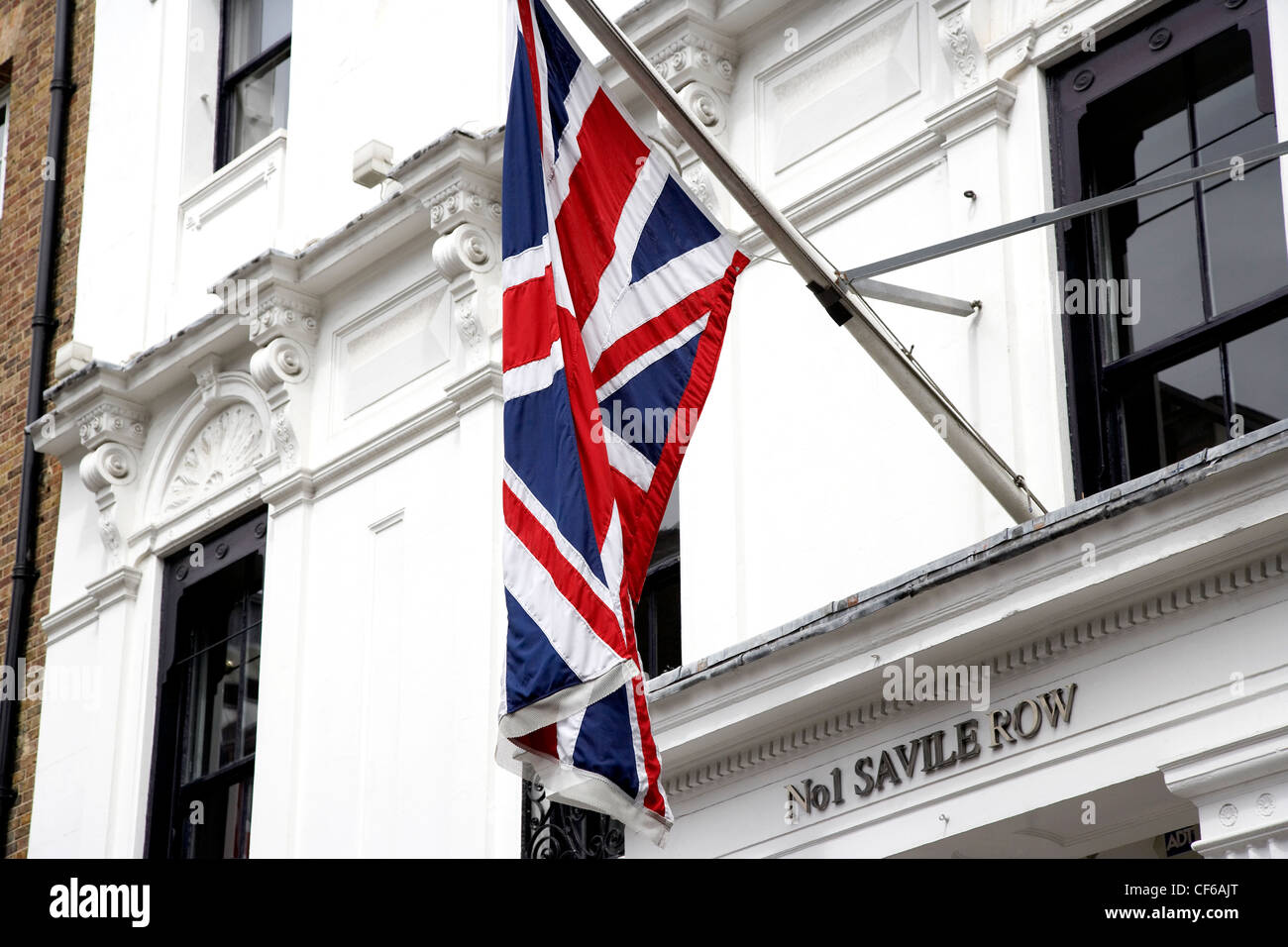 A Union Jack flag hangs above the entrance to number 1 Saville Row in London. - Stock Image