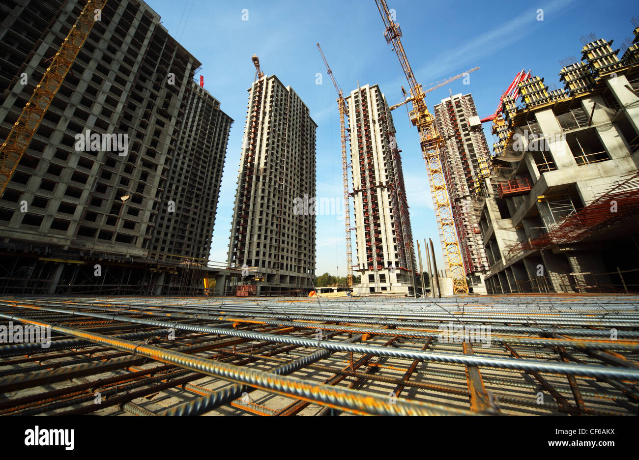 Between tall buildings under construction and cranes under a blue sky Stock Photo