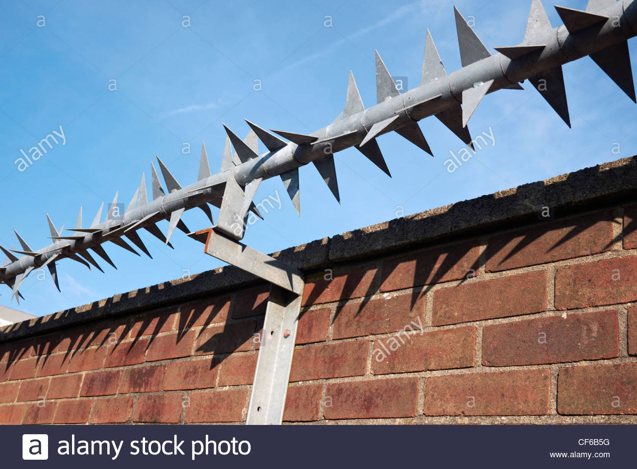heavy duty metal heavily spiked points security fence barrier on top of a brick wall - Stock Image