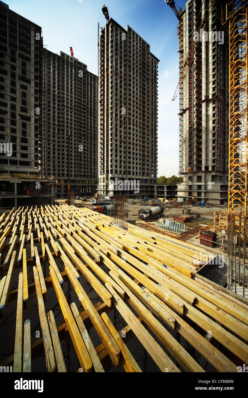 On wood planking between tall buildings under construction and cranes under a blue sky Stock Photo