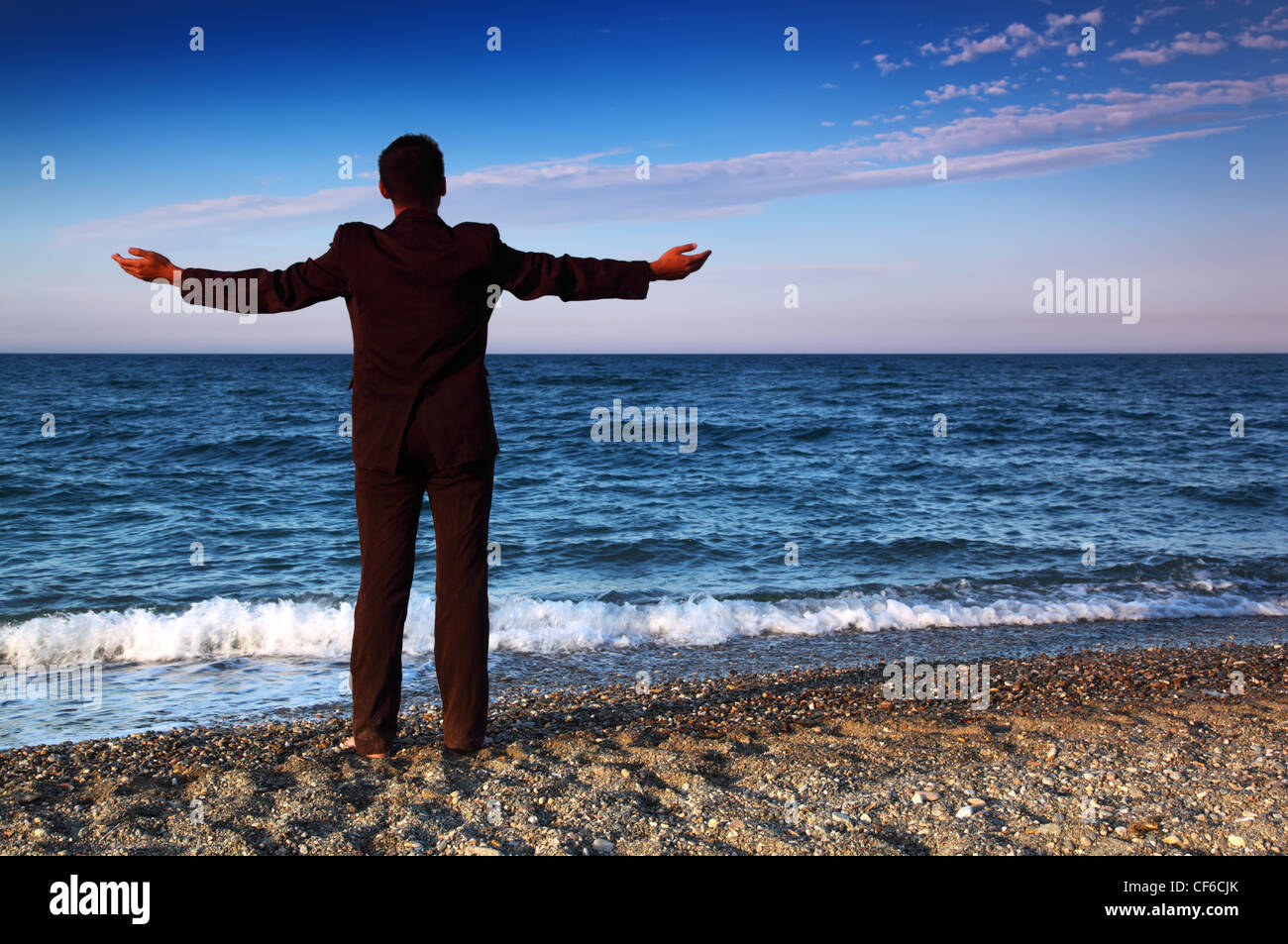 Barefooted man in suit stands back and open hands on stone coast at evening - Stock Image