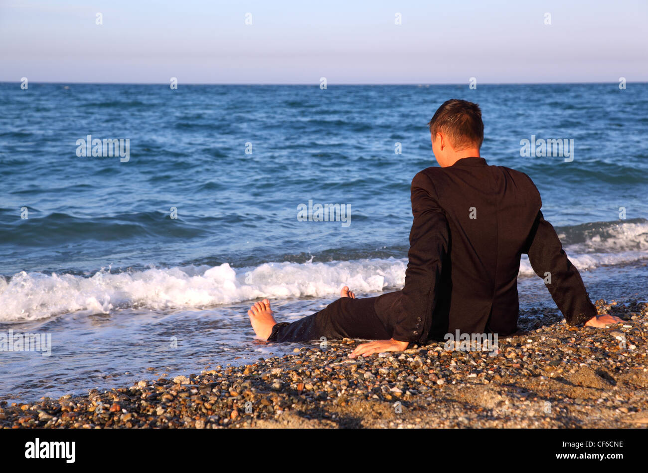 Barefooted man in business suit sits back on stone coast at evening - Stock Image