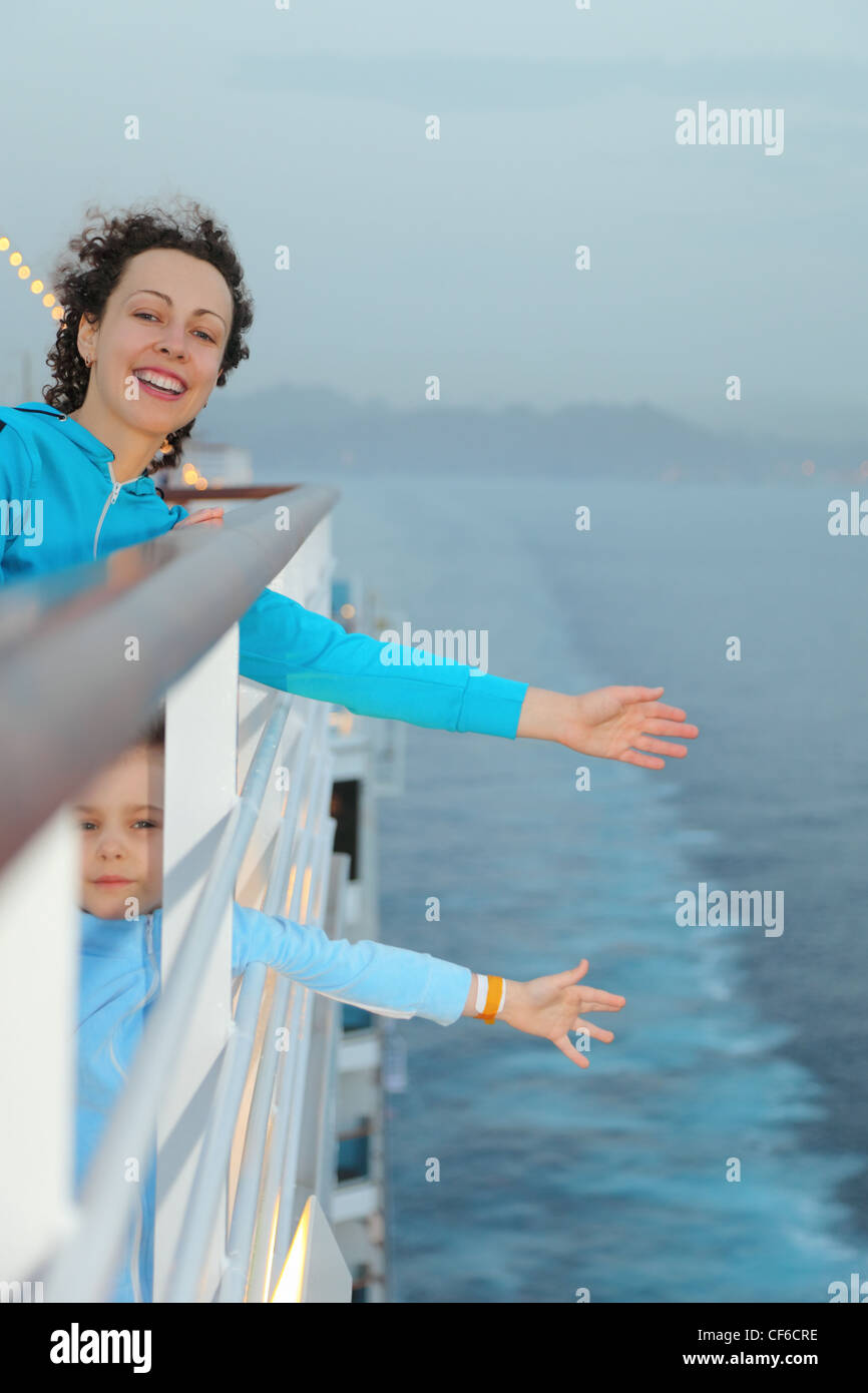 joyful beautiful woman with her daughter is standing on deck of cruise ship - Stock Image
