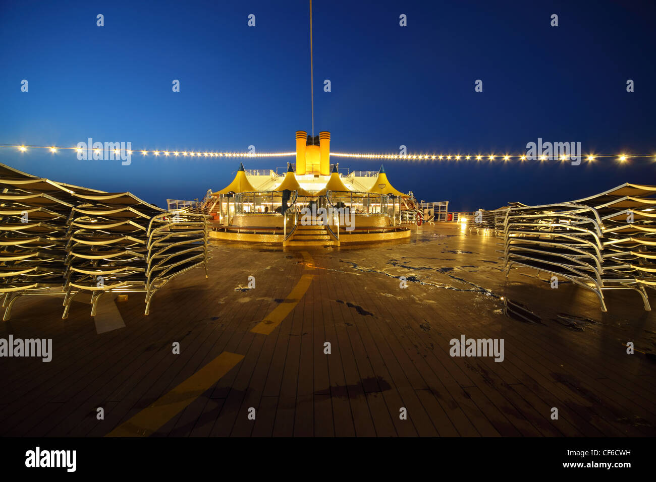illuminated deck of cruise ship at evening. bar and tables in center of image. - Stock Image