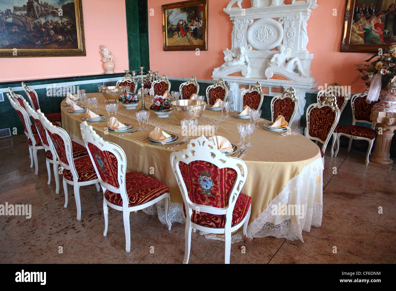 Big Oval Dinner Table With Empty Dishes: Plates With Placemat, Forks,  Knives And
