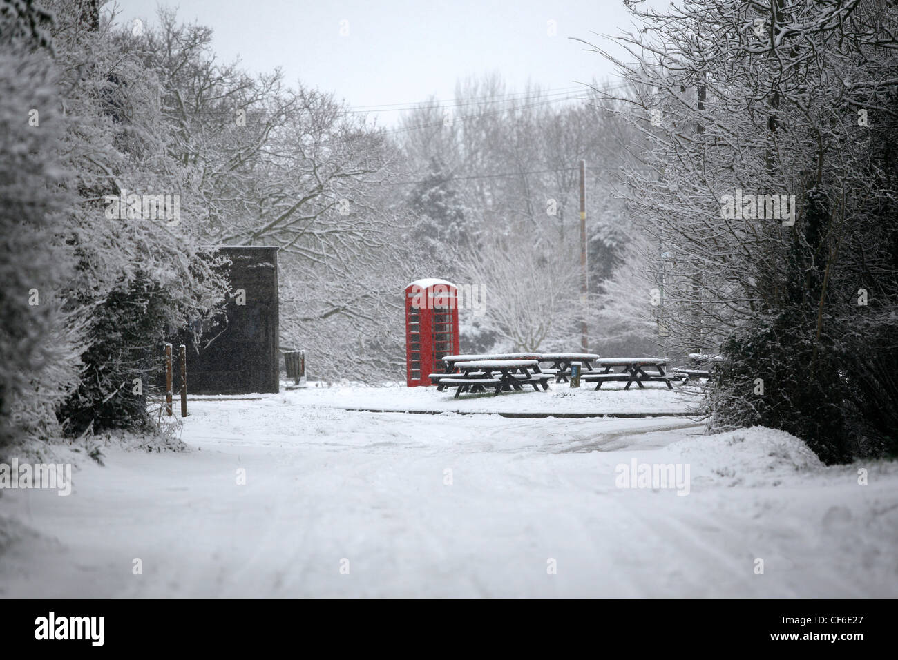 A village phone box in snow. The first standard public telephone kiosk introduced by the United Kingdom Post Office - Stock Image