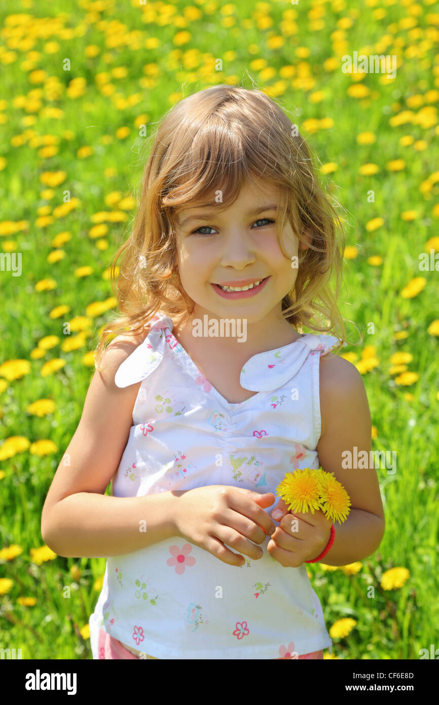 Little girl stands on  field and holds dandelions - Stock Image