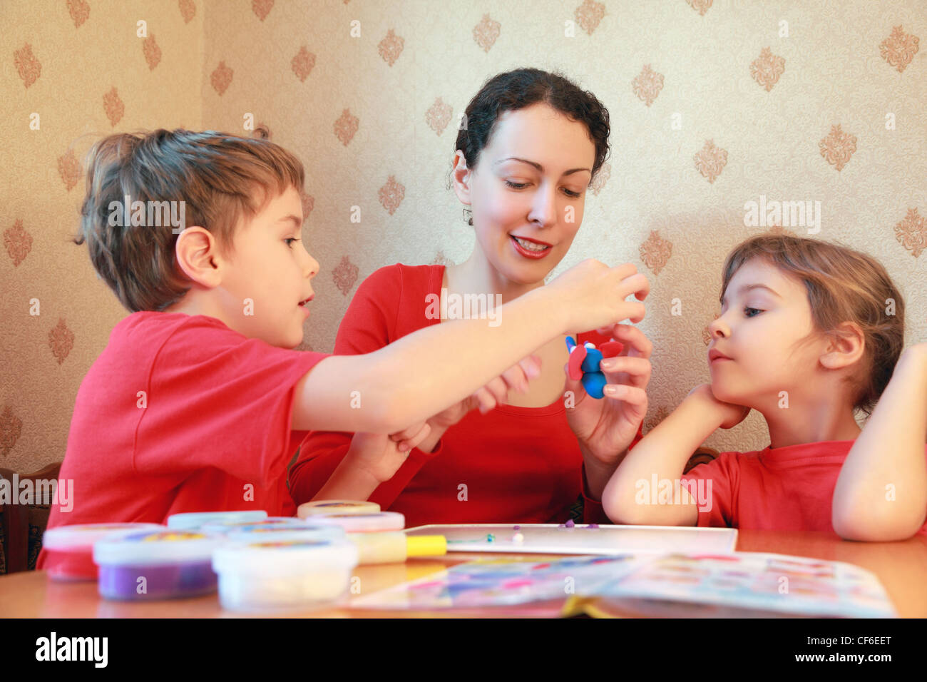 Mother and two children are at  table and model from plasticine, home-made elephant - Stock Image