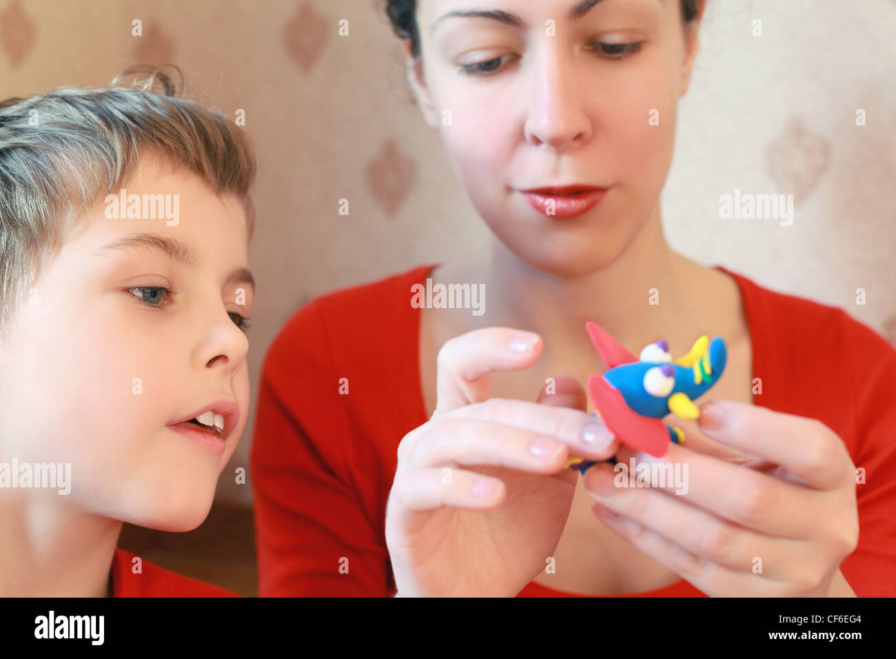 Mother and  son play with  home-made elephant from plasticine - Stock Image